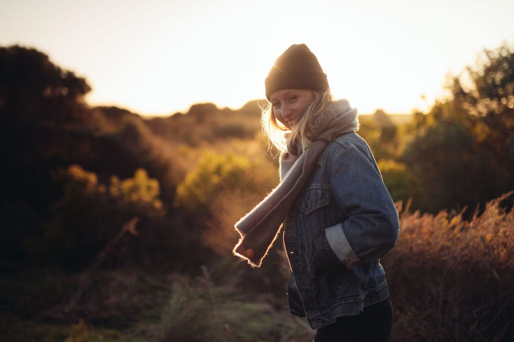 Image of a woman outside in a field at sunset. She is wrapped up in a warm hat and scarf. Gods grace can allow us the freedom to make a fresh start in the new year.