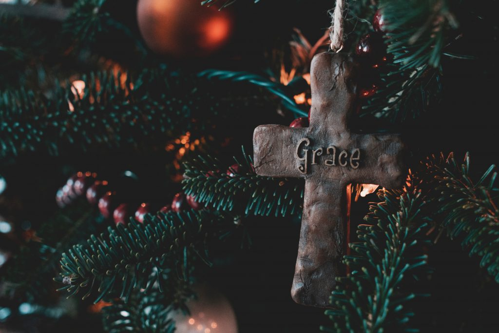 A cross with the word Grace written on it sits in a lit Christmas tree. Grace is one real gift of faith you could give this Christmas.