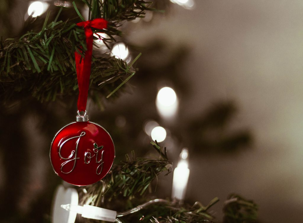 A red ornament with the word Joy written on it hangs from a Christmas tree branch with lights in the background. Joy is one real gift of faith you could consider giving this Christmas.