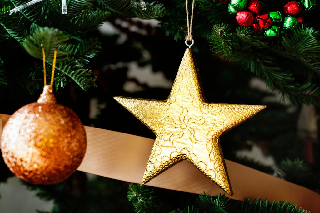 A golden star and an orange Christmas ornament hang from a decorated Christmas tree. Think and pray about which real gift of faith you could give someone this Christmas.