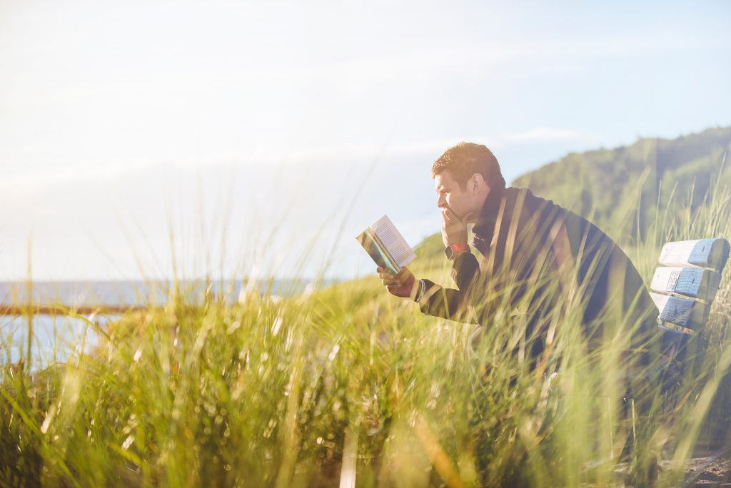 A man sits on a bench on a cliff over looking the sea. He is reading his Bible in search of answers to his big questions. The HelpFinder Bible can help you find those answers quickly.