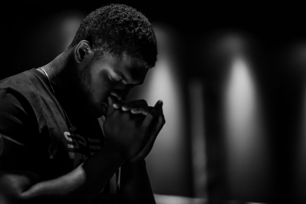 A young man clasps his hands together in front of his face, with his head bowed and sharp lights point down the walls behind him, out of focus. One of the ways in which can start to rely on God's promises is by praying for them.