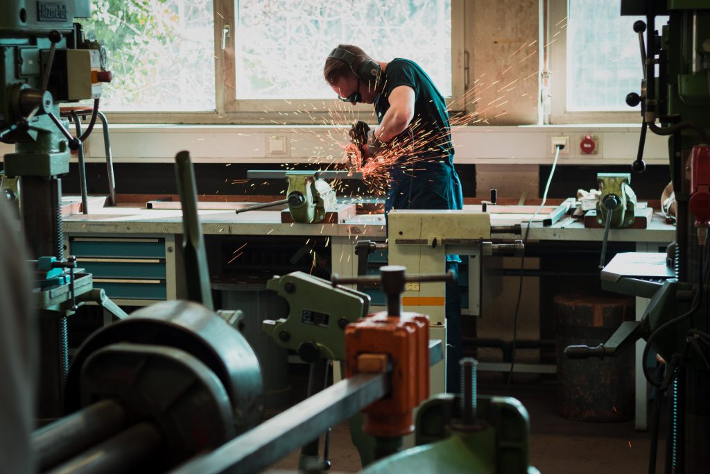 A man in goggles, ear defenders and an apron creates sparks that fly in his metal working shop. He is surrounded by tools and benches. We often just need to trust in God promises, relying on Him and demonstrating our faith in Him.