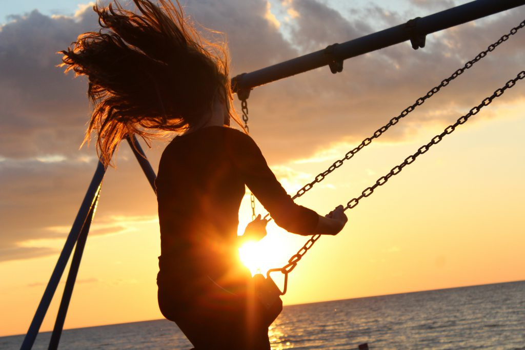 A young woman with free-flowing long hair swings on a metal play set next to the ocean. The sun is setting beyond her and the light catches in front of her lap as the swing descends. Here we look at five ways to start relying on God's promises.