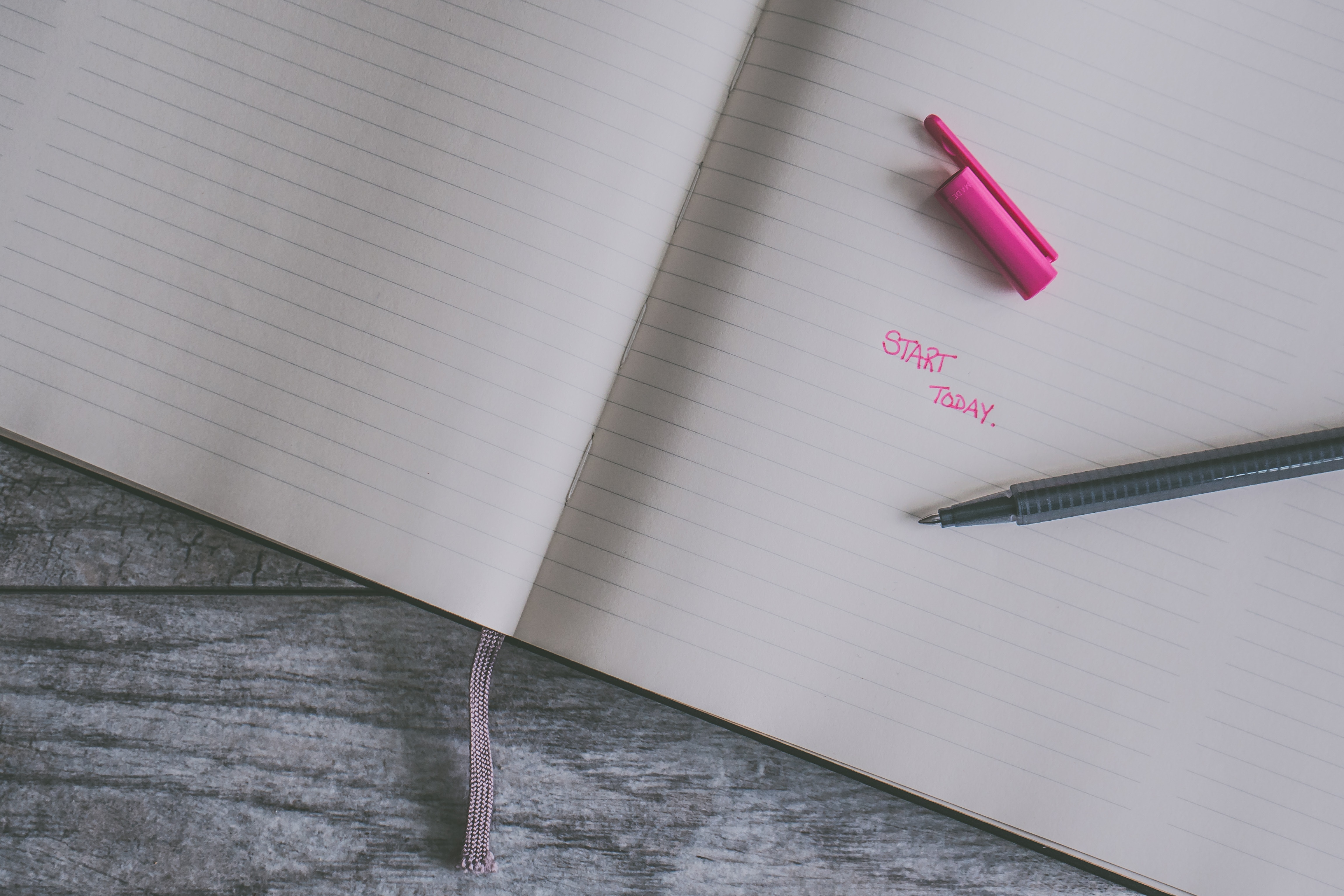 A plain notebook displays in pink ink the words written 'Start here'. Start now with your fresh beginning this year.