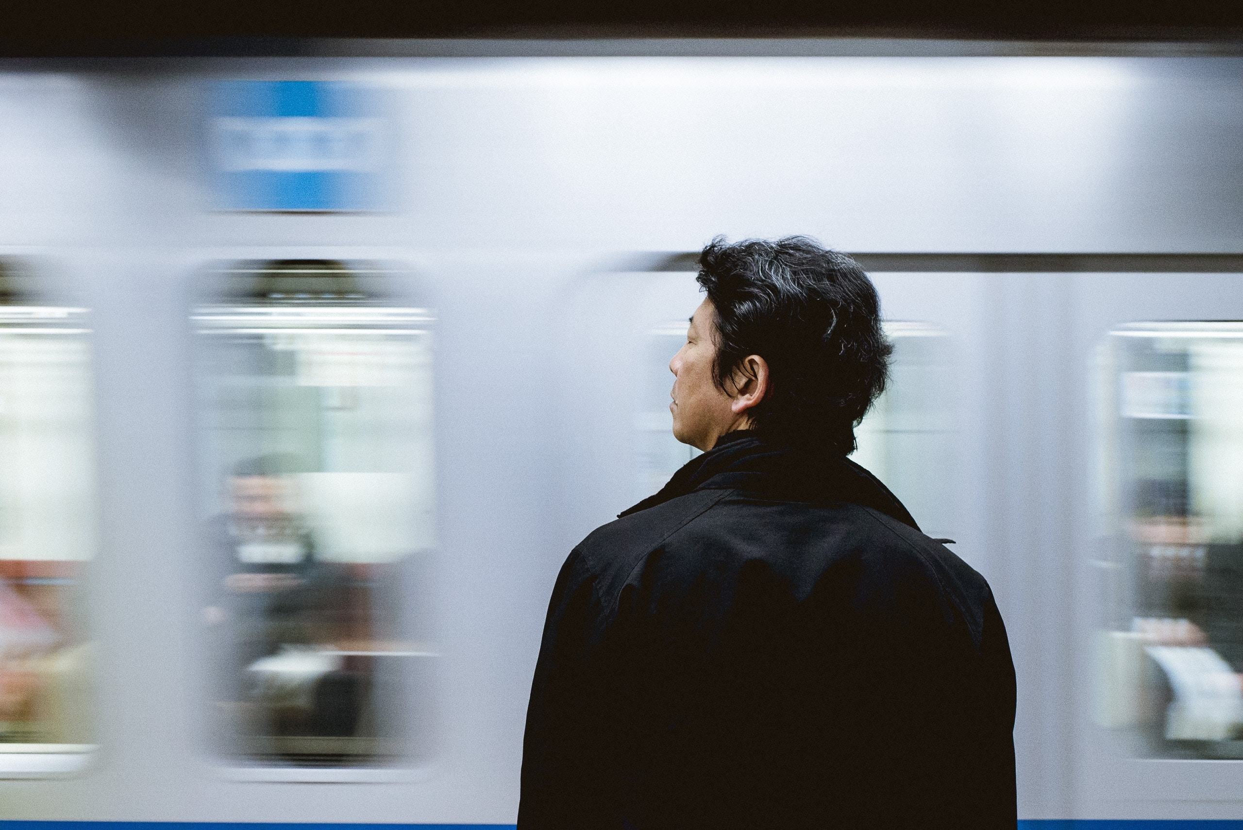 Image of a lone male standing by a fast moving train.