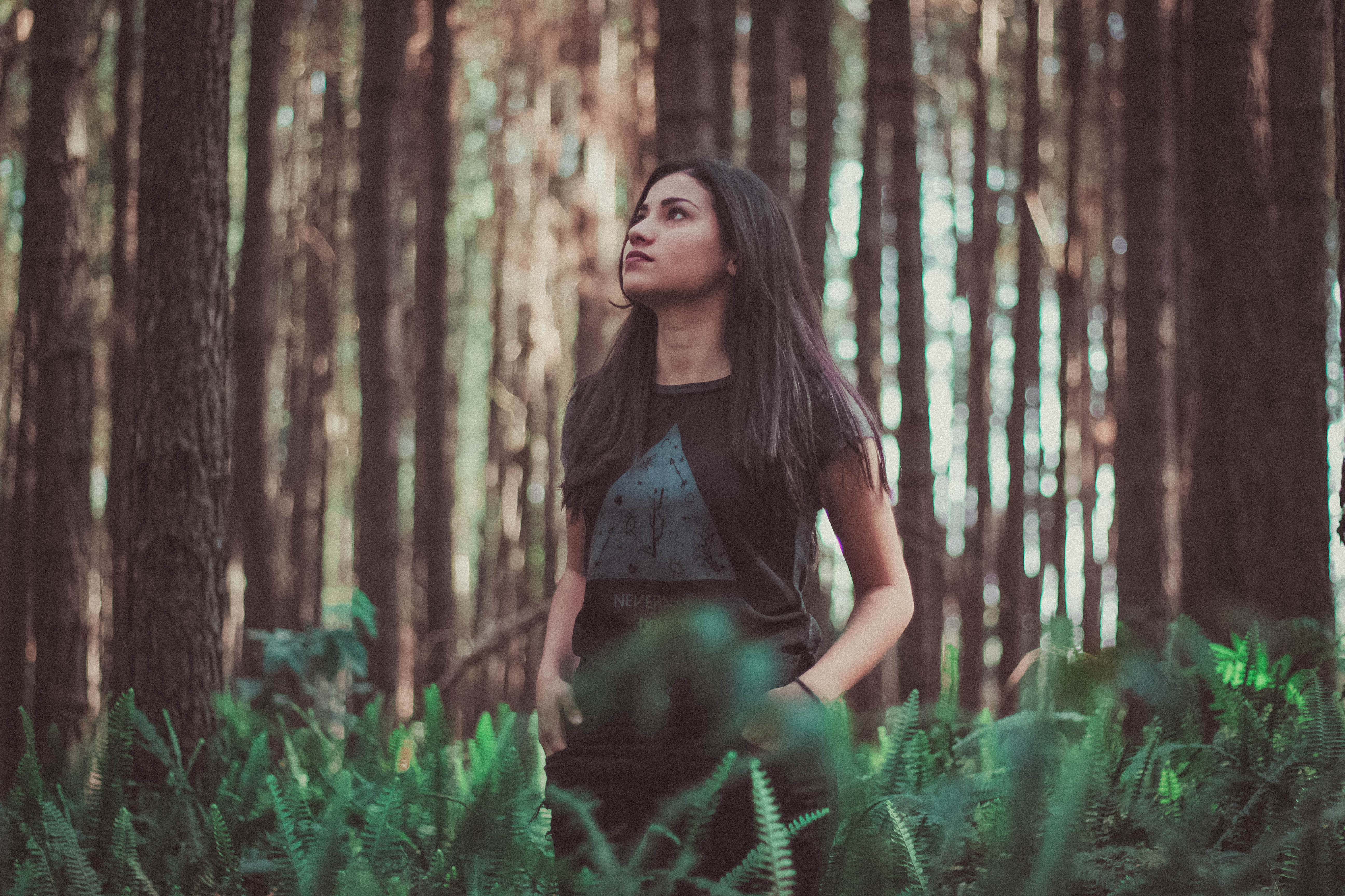 A young woman stands with her hands in her pockets, among ferns and trees in a forest. She is looking up towards the sky. She could be wondering if she can trust God. To her we would say yes!