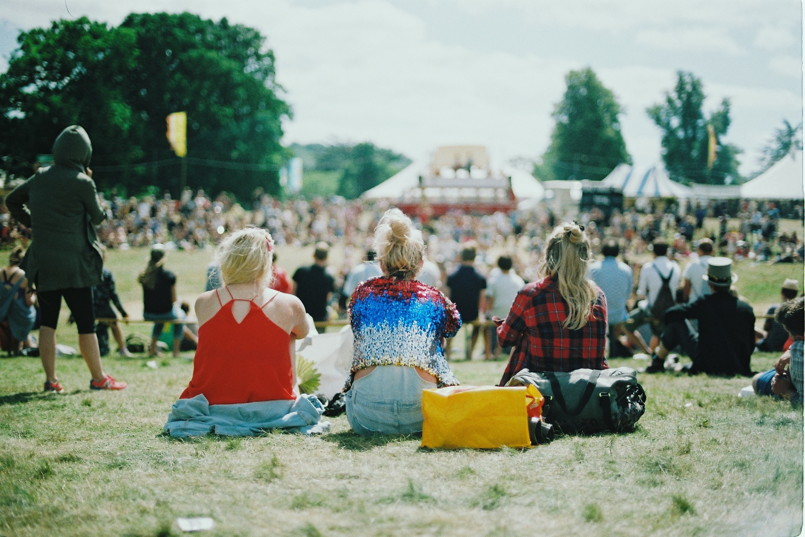 Three female friends sit on a field at a busy festival, with their backs to the camera. You can invite your non-believing friends to read the Bible with you and they, and you, will be blessed.