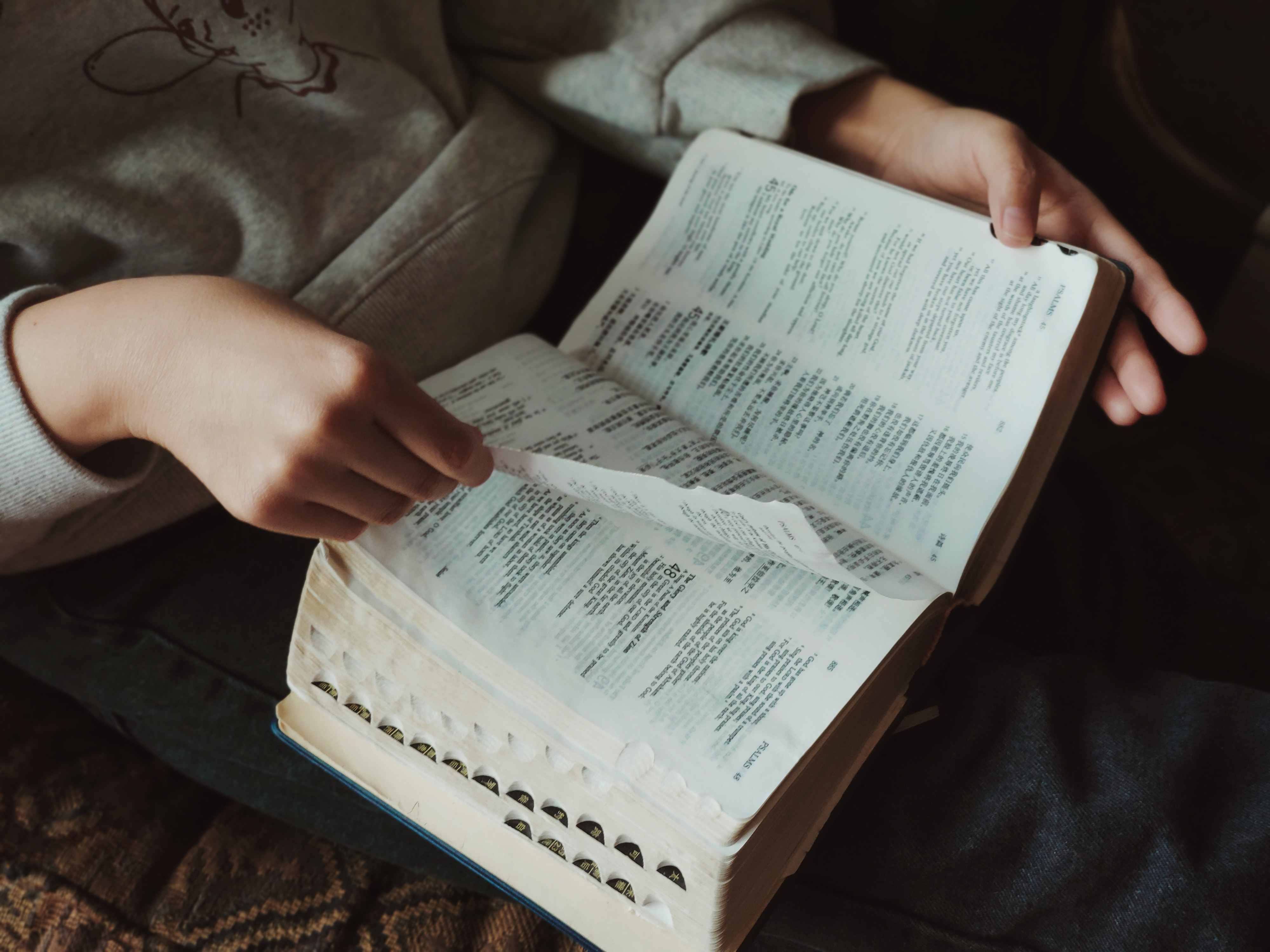 A person sits and reads their Bible, which we see in close up, on their lap. Reading the Bible with non-believer friends is a truly powerful way to share the good news with them.