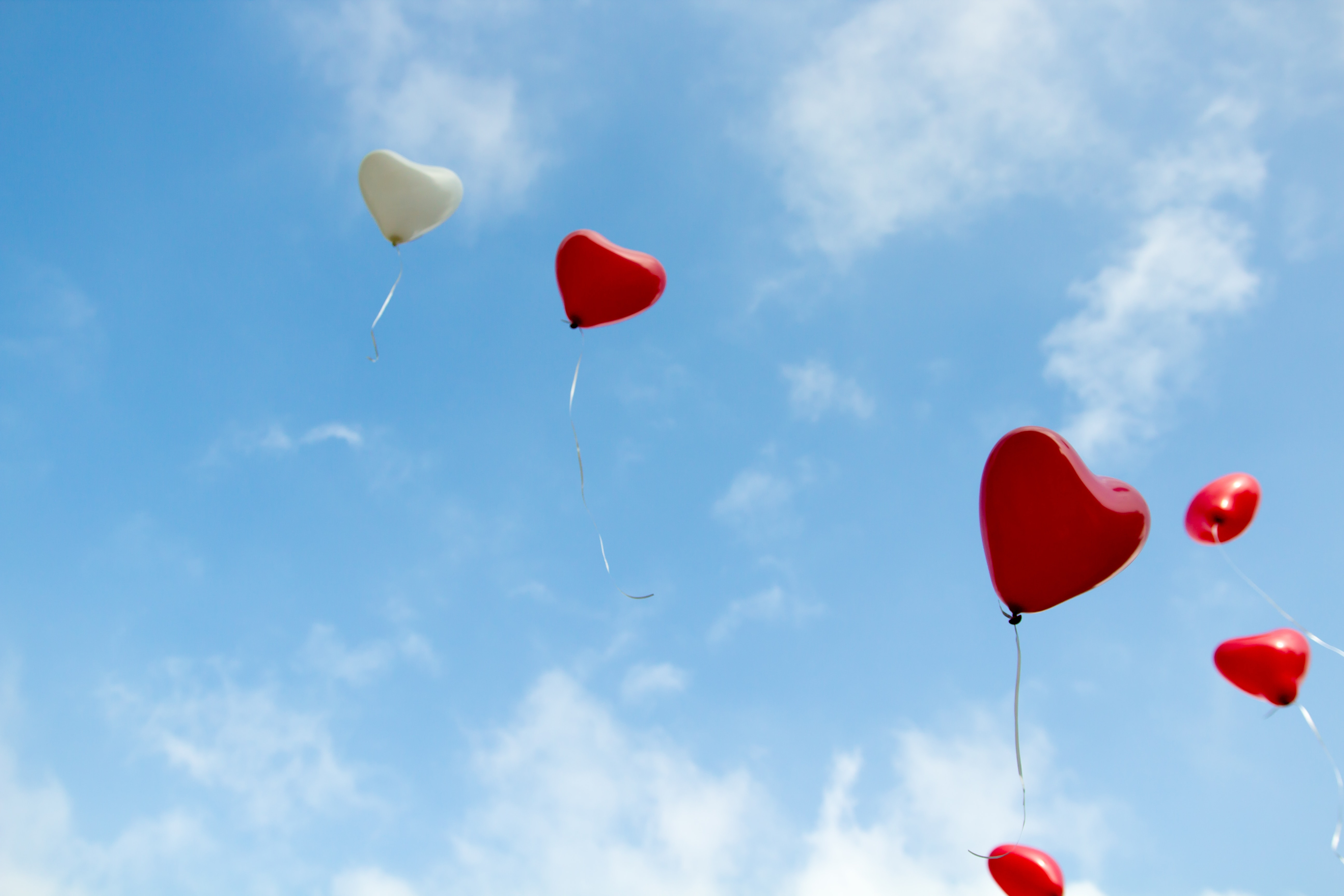Red and white heart-shaped balloons float up into a blue sky. As non-believer friends read and experience the Scriptures, God's love is revealed to them. It's essential that someone invites the to read the Bible though - that's you!