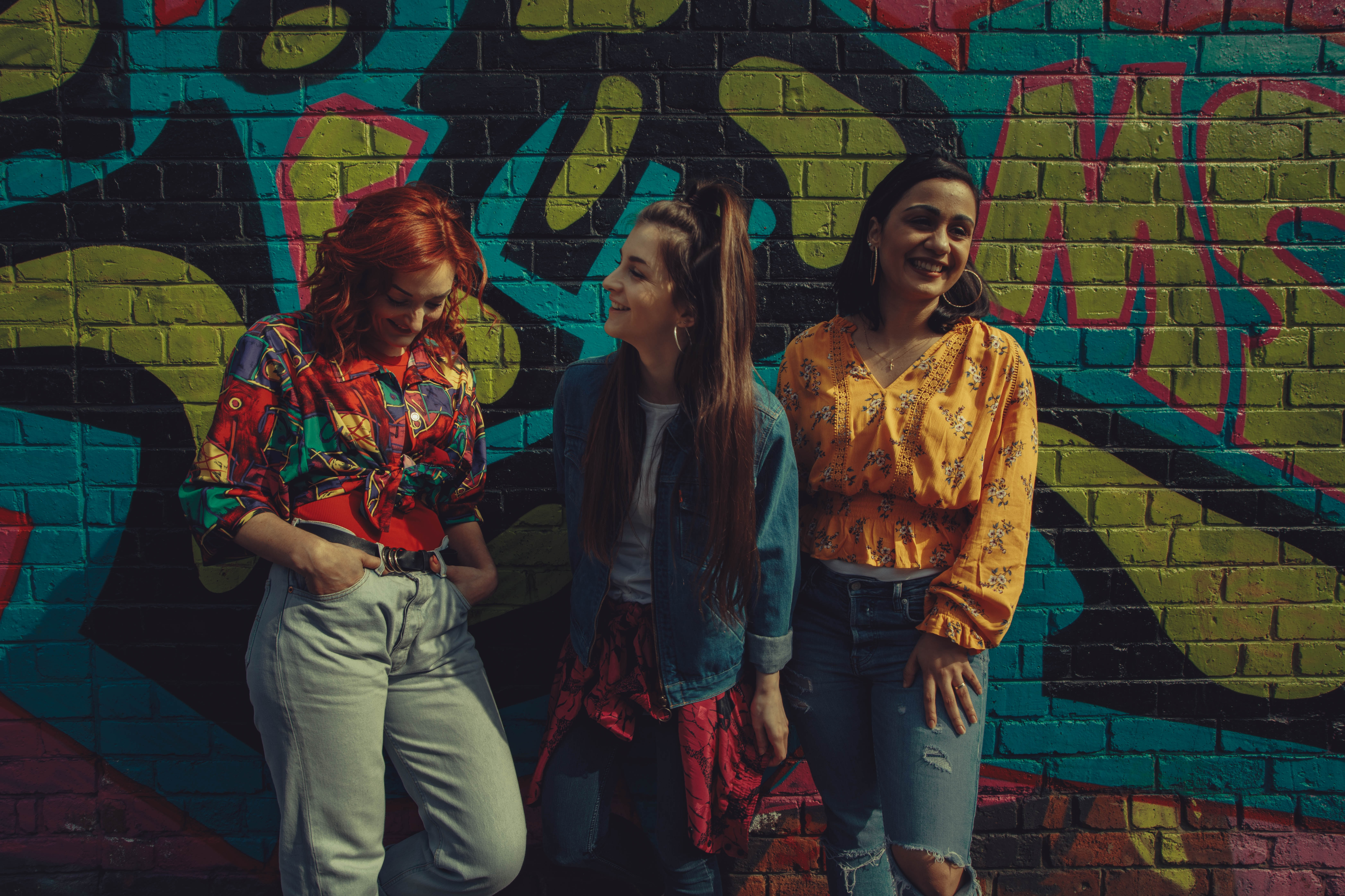 Three young women in colorful shirts and denim stand against a graffiti wall, they're all smiling. When you ask a non-believer friend to read the Bible with you, you can be sure that God's Word will speak to them in the way they personally need it to.