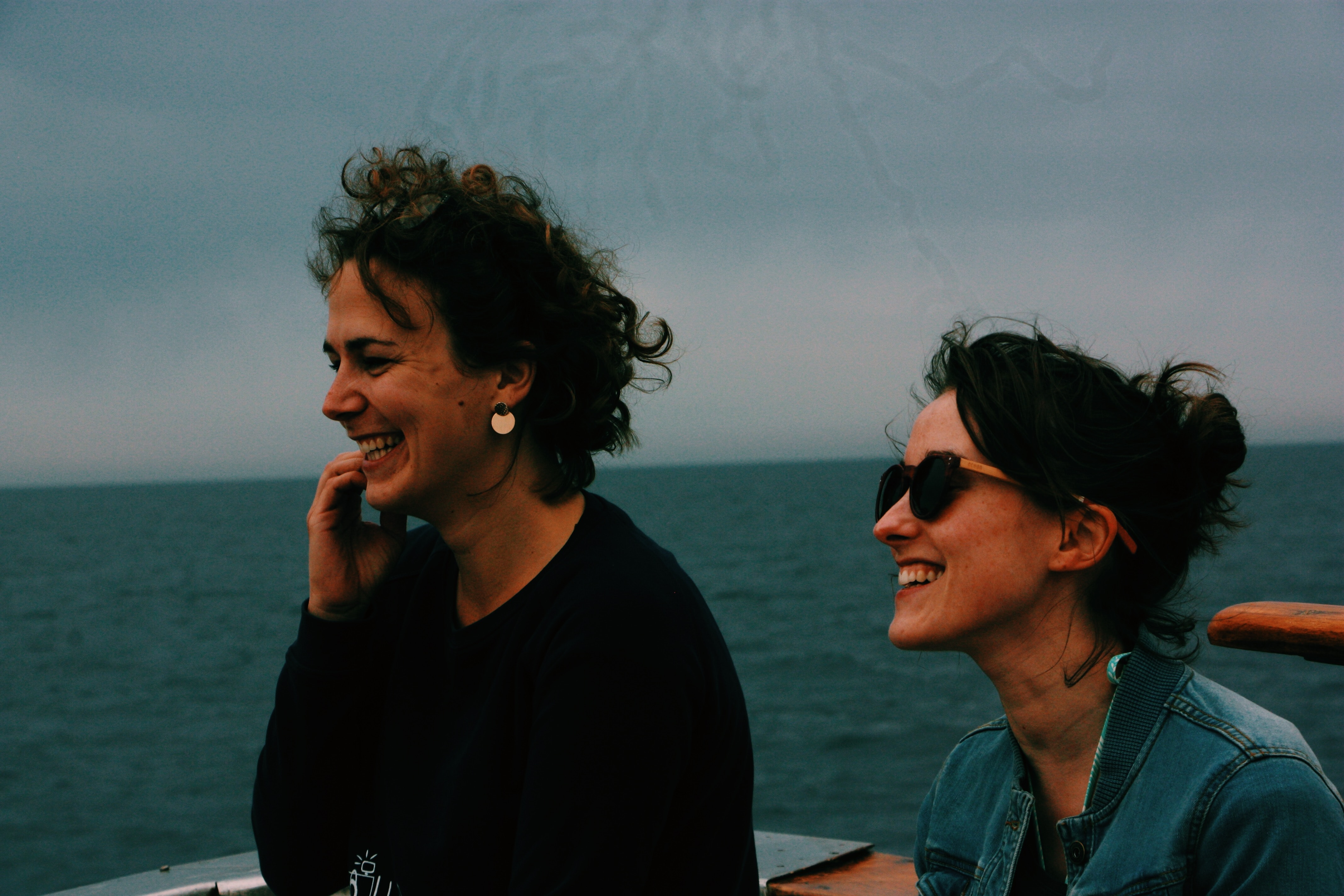 Two women stand smiling on what appears to be a boat on the ocean. How do you casually ask someone to read the Bible with you? This article explores options for inviting non-believing friends.