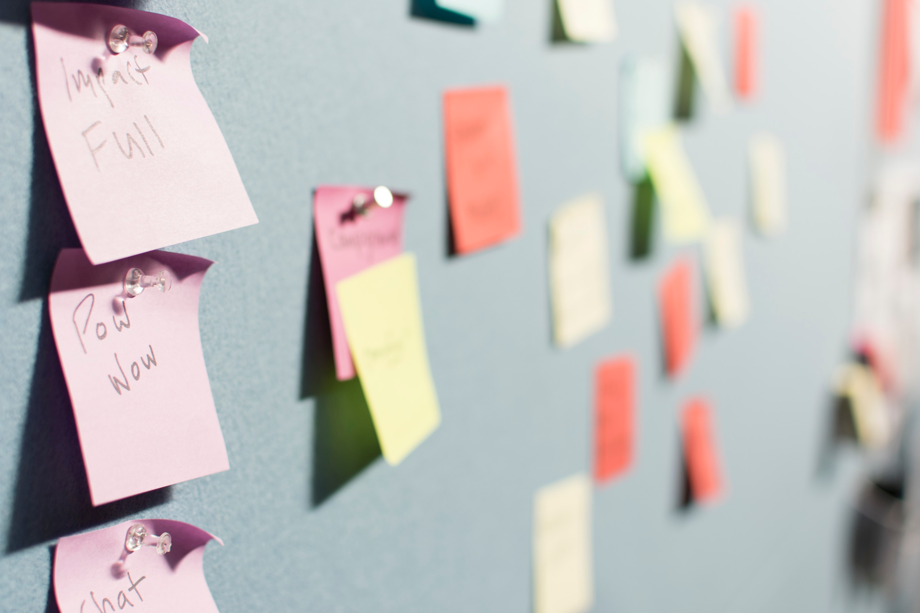 A number of colorful sticky notes are pinned to a wall. Asking questions to reflect back on the Scripture you've just read can help your non-believer friend find the meaning in the Word.