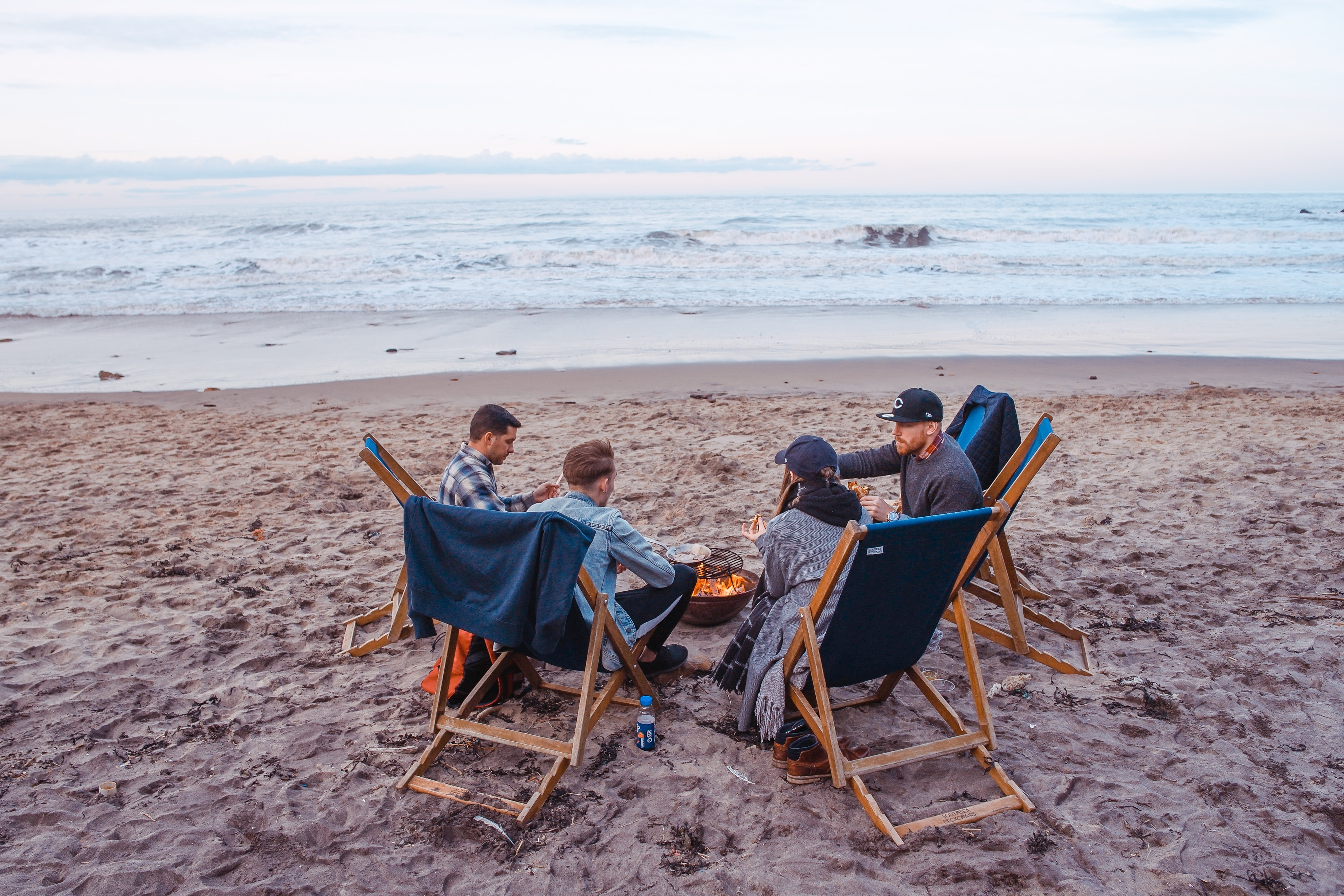 Three male and one female friend wit around a camp fire on a beach at dusk. They have prepared food and are eating together. While it's not always easy to invite non-believer friends to read the Bible with you, God will guide your time.