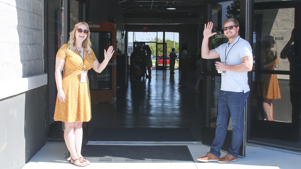 A man and a woman stand in the entrance to their church waving, ready to joyfully greet people as they enter. they are using their spiritual gifts to help in their church.