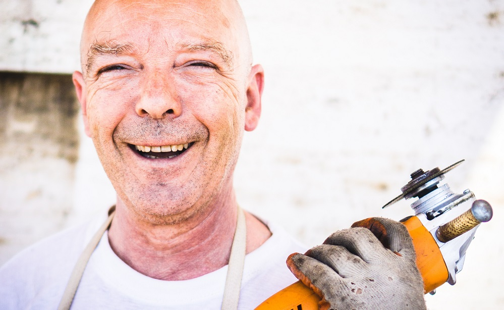 A happy man holds a buzz saw in close up. He is using his spiritual gifts by performing construction jobs, either around his church, or in ministry.