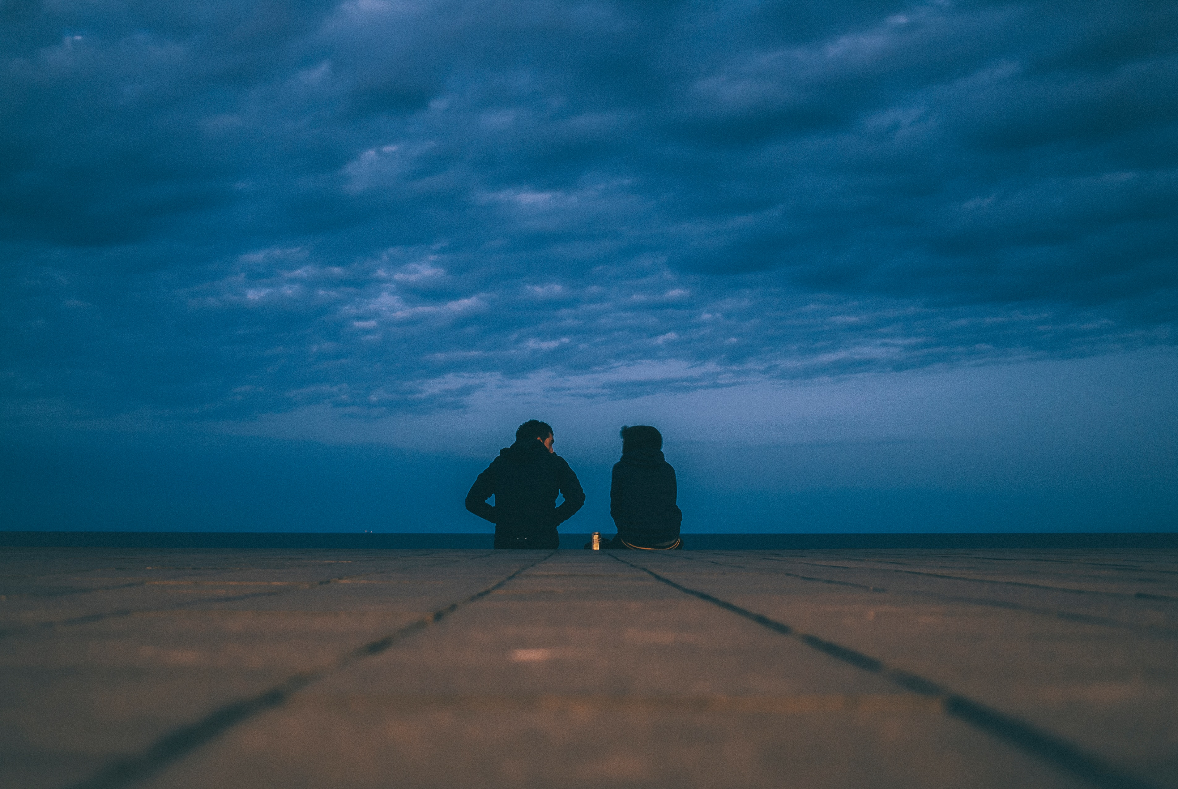 Two friends sit on the end of a dock, chatting with each other. They're wearing coats and the sky looks dark and moody. Who is seeking God's wisdom through you?