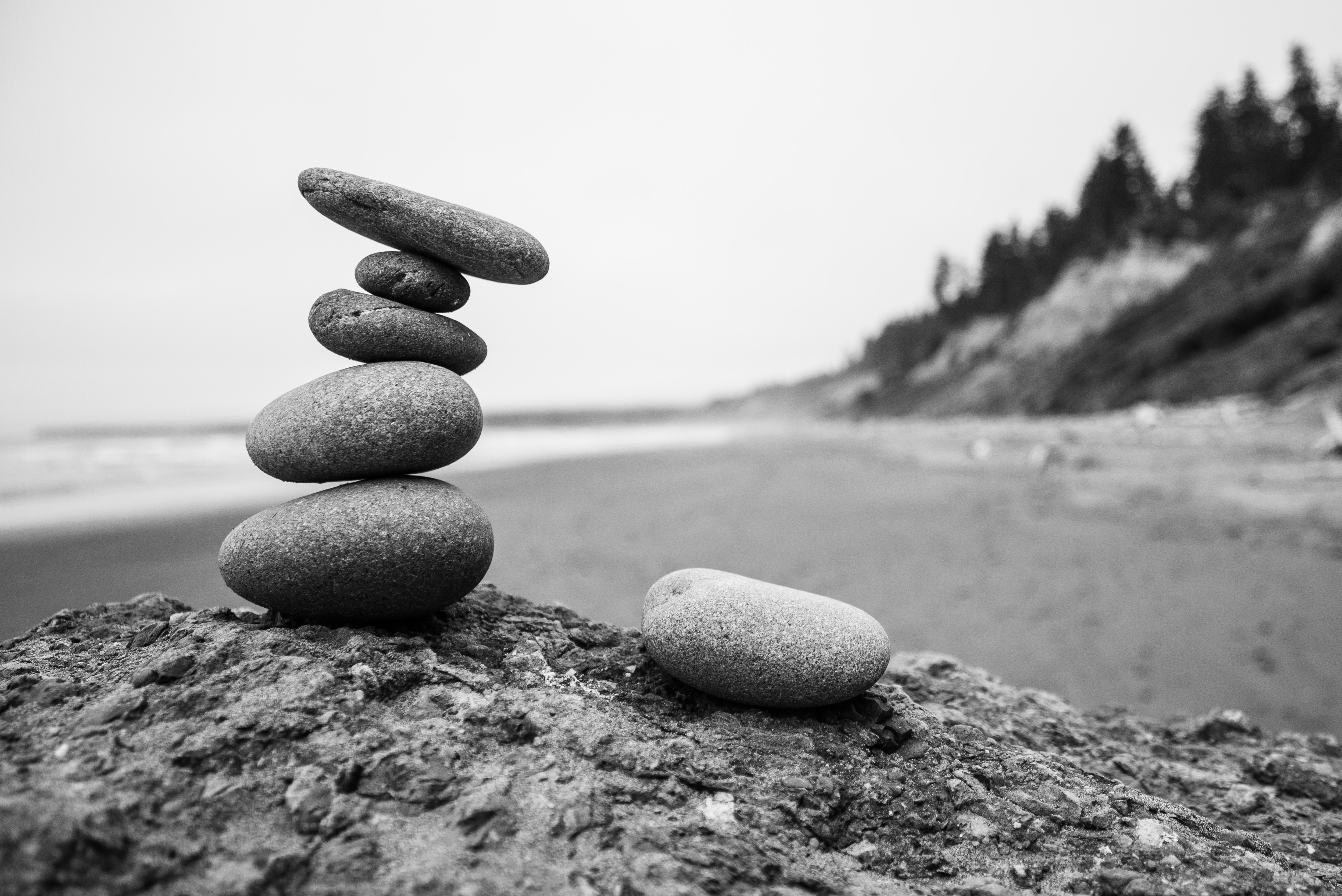 A pile of smooth stones stand on a sandy beach in a black and white photograph. God gave us the Proverbs to teach us and provide us with wisdom for life.