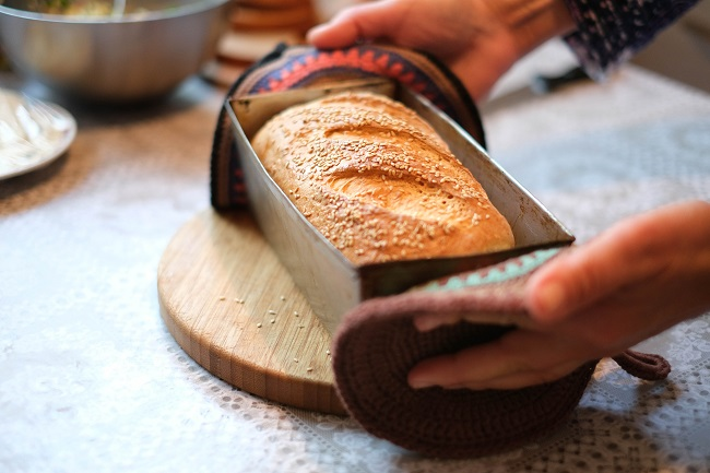 A pair of hands places a freshly baked loaf of bread, still in it's baking tin, on a table. The talent of cooking or baking pairs very well with the spiritual gift of hospitality!