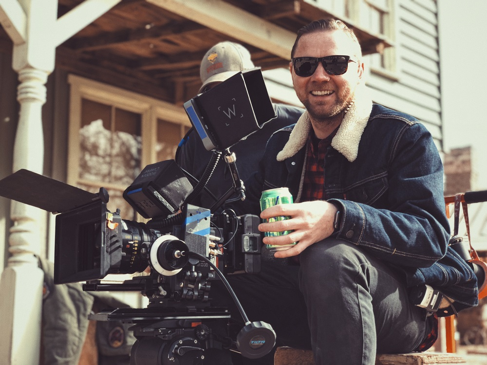 A man sits behind a professional film camera. He is holding a can of drink, wearing sunglasses and smiling. He uses his spiritual gifts to help create video content for his church.