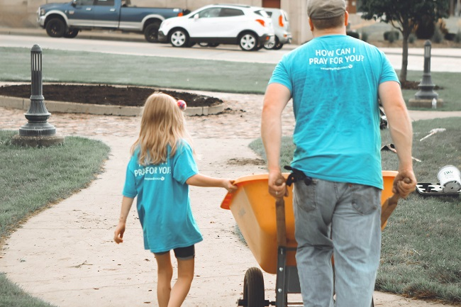 A father and daughter, wearing blue volunteer t-shirts, move a wheelbarrow as they use their spiritual gifts of helps to volunteer on a project.
