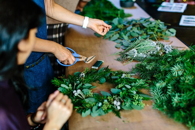 Two people work on wreaths with lush green leaves, crafting beautiful decorations. Matching up your spiritual gifts, with your personality, passions and preferences for format, will lead you to deep joy and you'll be helping to move the Kingdom forward!