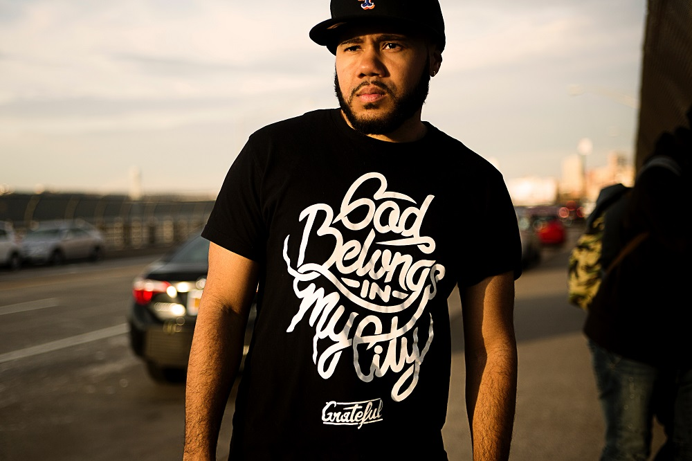 A young man in a black baseball cap and black slogan t-shirt, stands in the street. His t-shirt says 'God belongs in my city'. An ordinary person embracing the spiritual gifts God has given them, can become an extraordinary person in their use.