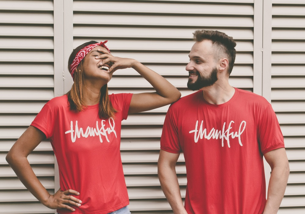 A man and a woman pose, laughing, in bright red t-shirts that say 'Thankful' on them. They become extraordinary when they use their own spiritual gifts in service.
