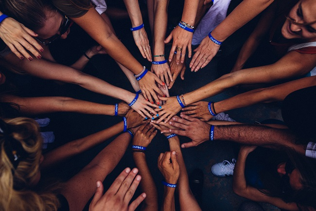 A large group of people all have their hands in for a team hand huddle. they're all working together, using their various spiritual gifts, for the good of the Kingdom!