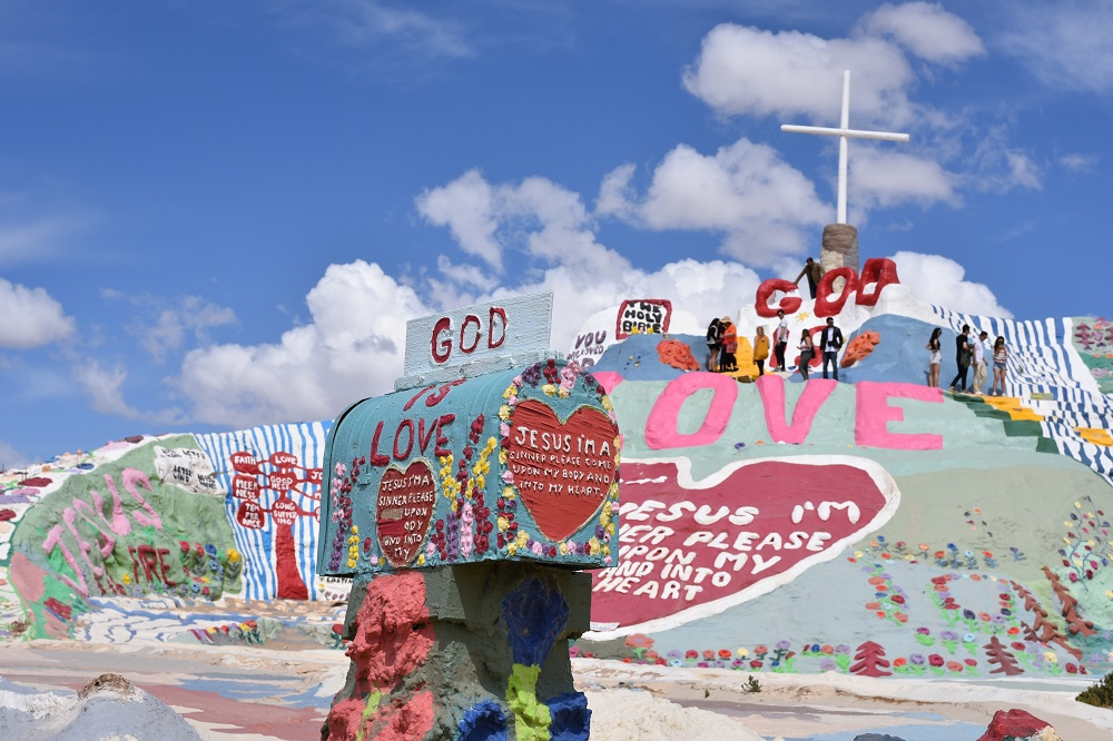 We see a large hill covered in a colorful mural with a tall white cross on it and a painted mailbox in the foreground, all proclaiming the love of God and Jesus. The artist who created this extraordinary piece is putting their spiritual gifts on full display!