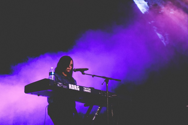 A woman plays on an electric keyboard on stage with smoke behind her lit in purple. She is using her talent and skills to inform her spiritual gifting and find the very best place for her to exercise them.