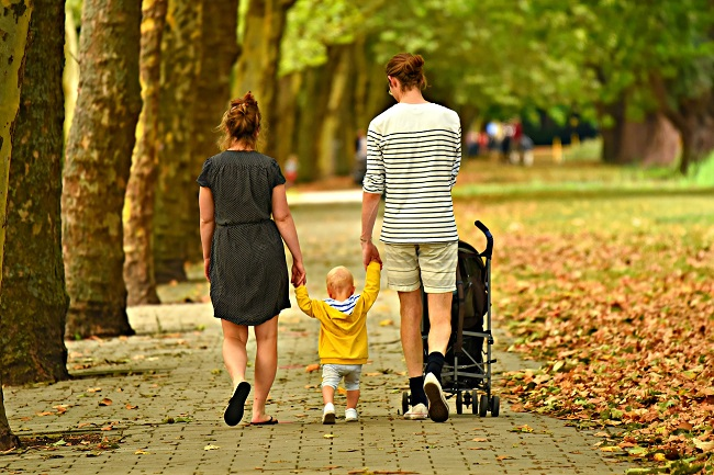 Parents walk with their small child on a path surrounded by trees and grass. Sometimes we use our spiritual gifts to serve those closest to us.,