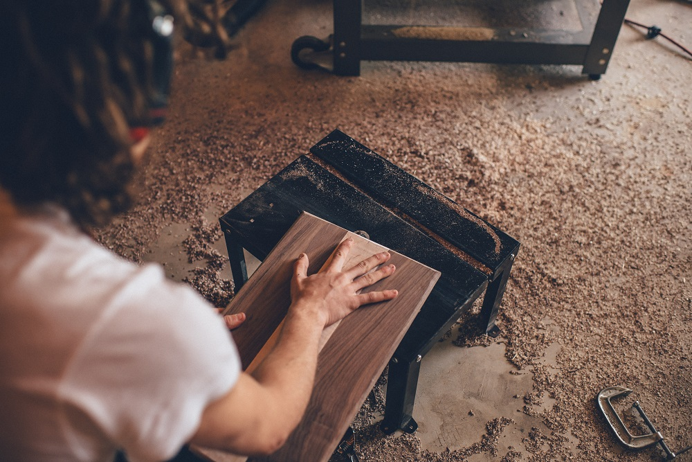 A carpenter moves a block of wood over a metal stool on the floor of his woodworking shop. He is using his spiritual gifts, and putting them to good use for the Kingdom.