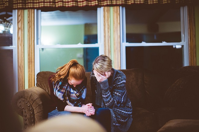 Two young woman sit on a couch with their heads bowed in prayer. Faith, healing and mercy are all spiritual gifts they may be using in this moment.