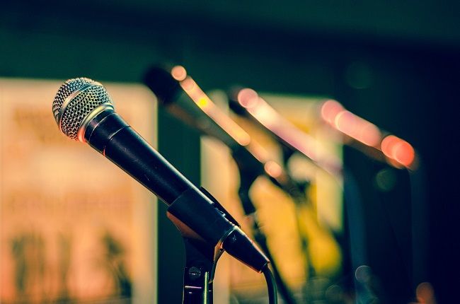 A microphone is photographed up close with a row of microphones behind it, out of focus and lit with beautiful, moody colors. Teaching is a spiritual gift and can involve speakign in front of lots of people, or just one person. It all counts!