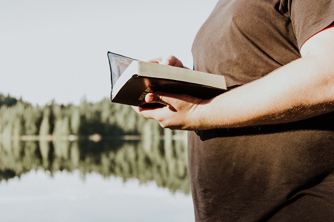 A Bible reader in a brown t-shirt stands next to a still lake with their Bible open and the sun illuminating them. To abide in Christ is to walk close by Him, and by reading the Bible daily we can remain close to Him.