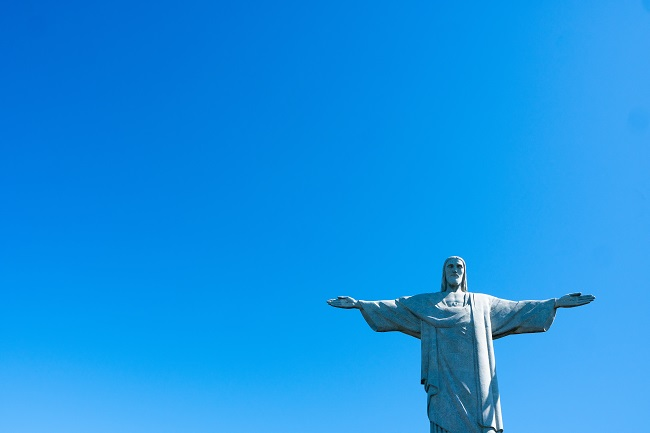 The statue of Christ the Redeemer is photographed from below, with a brilliant blue sky behind it. In order to abide in Christ, we should live by His Word.