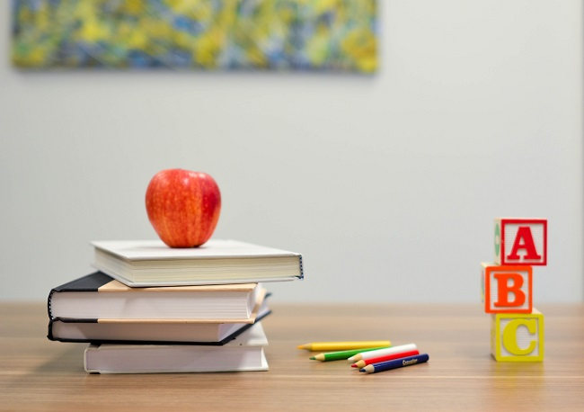 A teacher's desk is adorned with a pile of books, pencils an apple and ABC blocks. It's important for Christians to continue learning throughout life so that we might remain close to Jesus.