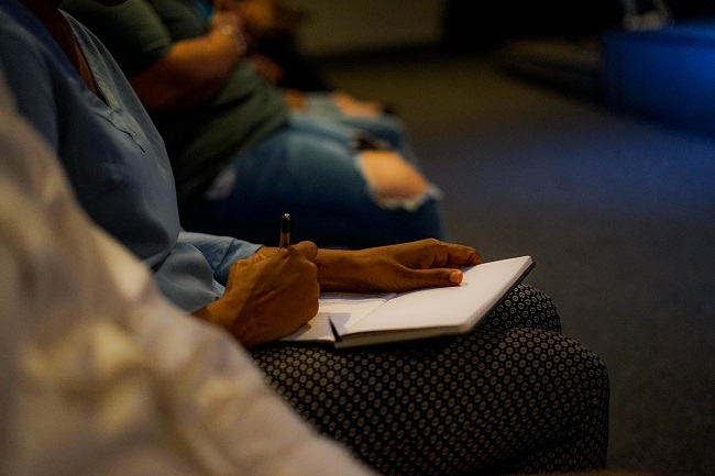 We see a man's hands writing in a book as he sits listening to a lecture with people on either side of him. He is learning in order to follow Jesus closely.