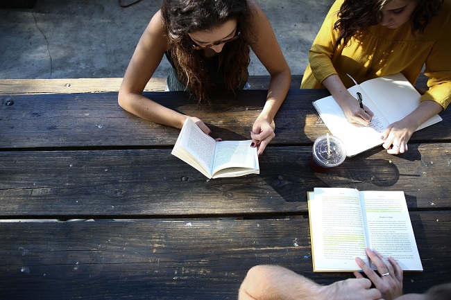 Three friends sit around a wooden bench with books, making notes in them, studying the Bible to keep learning about Jesus.
