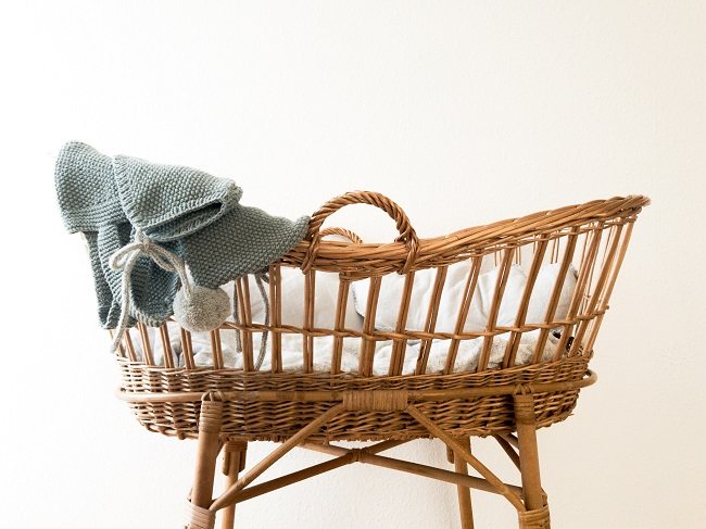 A wicker bassinet with white bedclothes and blue blanket hanging over the top end of it, is pictured against a white background. Why did Jesus come to us as a baby? this article seeks to answer that question.