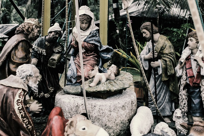 A nativity scene with stones and statues is pictured, with baby Jesus in the center.