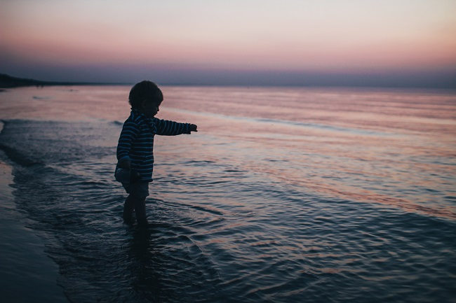 A toddler stands on the edge of the water on a beach at sunset. Why did Jesus come to Earth as a child?