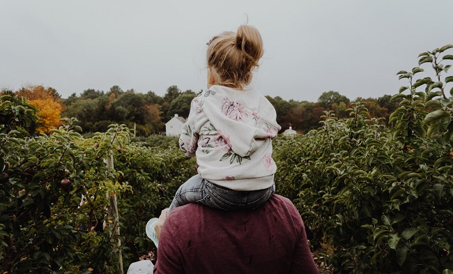 A young girl sits on her father's shoulders as they walk around a field of fruit bushes. there is a farm house in the distance. God protects His children and loves them just as a father on Earth would. That is why He became a man, to save them from a life in eternity without Him.