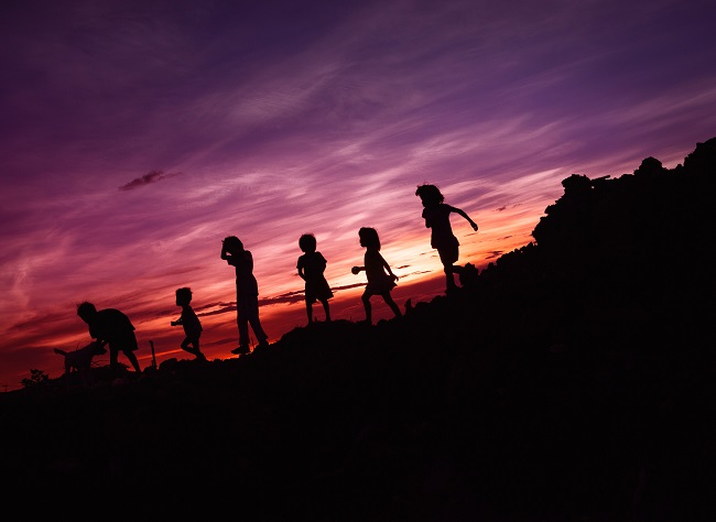 Several children are seen in silhouette against a pink sunset. they appear to be playing on rocks. God created man to be His children and had to become man in order to save them.