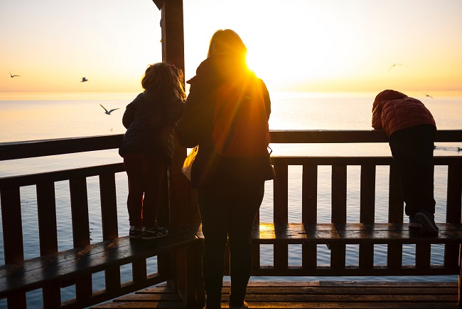 A mom and her children stand together ona balcony was the sun sets over the ocean in front of them. The sun hits her shoulder and we see the family in silhouette. Heaven came down to earth to save God's children, in the form of a man.