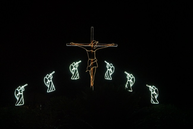 Lights against a black background depict the crucifiction of Jesus, with angels on either side of him. Why did Jesus come to earth? Read this article to find out!