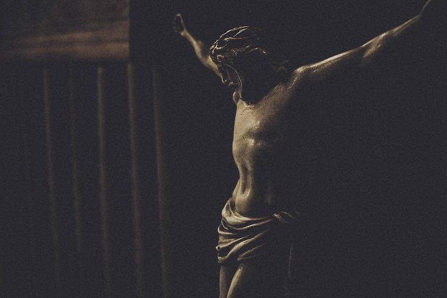 A statue depicts the crucifiction of Jesus. Why would Jesus come to earth knowing that He would have to suffer for us?
