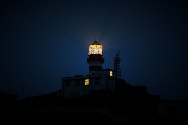 A lighthouse shines its beam of light through a dark sky. Jesus came to earth as our beacon of light!