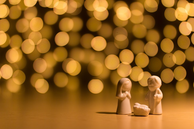 A small stone nativity sits on a table in front of glittering lights in the background. Jesus came to earth to save us!